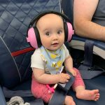 White baby girl wearing pink ear defenders
